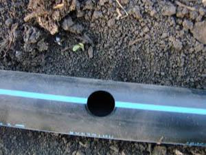 Отверстие в магистральной ПНД трубе для монтажа фитинга с резинкой